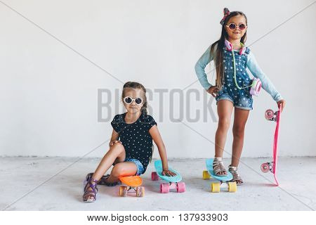 Two 7 years old children wearing cool fashion jeans clothing posing with colorful skateboard in white studio, urban style