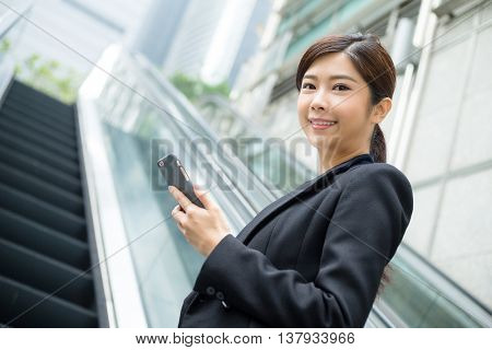 Business woamn holding cellphone and standing at escalator