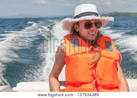 Young woman on a speed boat in a life jacket on a background foamy trace of the boat.