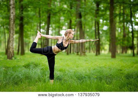 Nature yoga session in beautiful green polish woods between trees. Warrior pose - Virabhadrasana