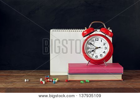 Back to school. Red alarm clock books stationery buttons and a sketch pad on the table in the background of a school blackboard.