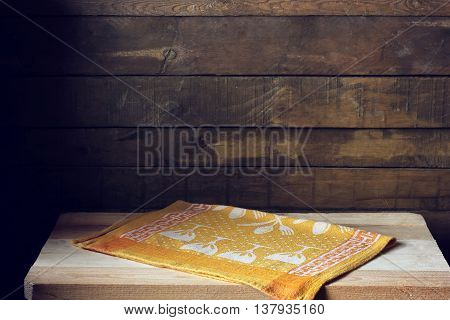 Empty wooden table with yellow towel in the background of the rough Board. Empty space for Your...