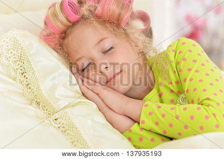 Happy cute little girl in hair curlers sleeping in her bed