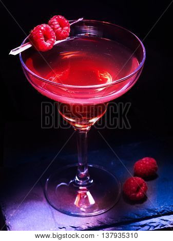 Raspberry martini cocktail alcohol drink with raspberries on black background. Cocktail martini card.