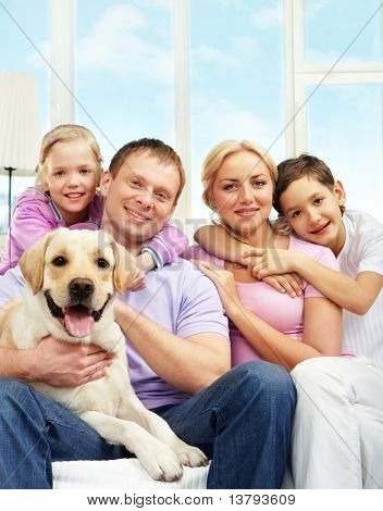 A young family of four with a dog sitting on sofa, looking at camera and smiling