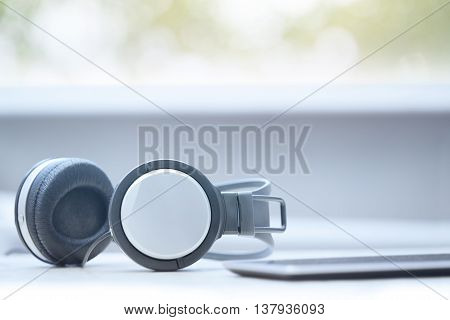 Headphones and digital tablet at office. Horizontal photo