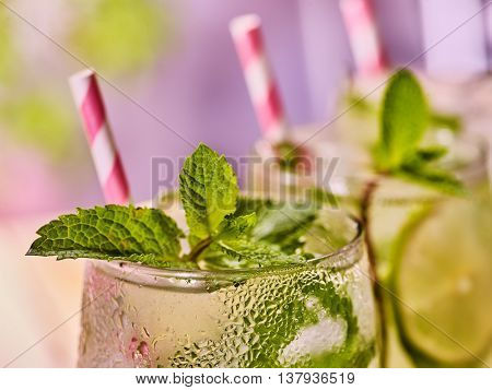 Alcohol drink. On wooden boards part of three glasses with alcohol drink and ice cubes. A drink number seventy six cocktail mohito with straw and mint leaf. Country life. Light background.