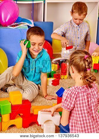Group children game blocks on floor in primary school. Top view of children in school.