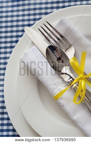 Table setting with blue checkered tablecloth white napkin and silverware