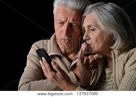 Portrait of a sad senior couple with phone