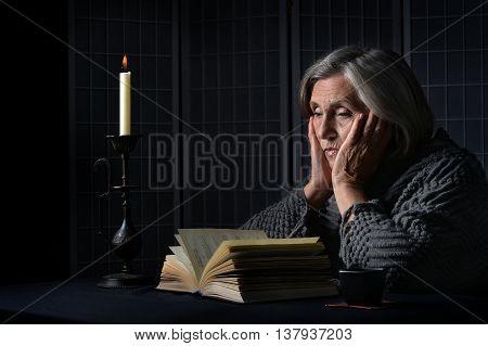 Portrait of a sad senior woman with book
