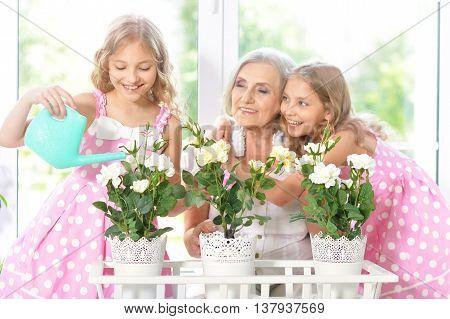 Old woman with tweenie   girls watering flowers at home