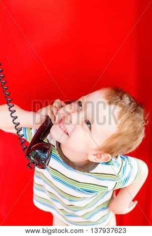 funny kid talking on the phone in telephone box. concept of sharing emotions, impressions and feelings. happy child holding a black telephone handset and wait for a phone call in red telephone booth.