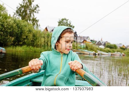 boy floats on a rowing boat to the shore. child confidently controls rowing boat