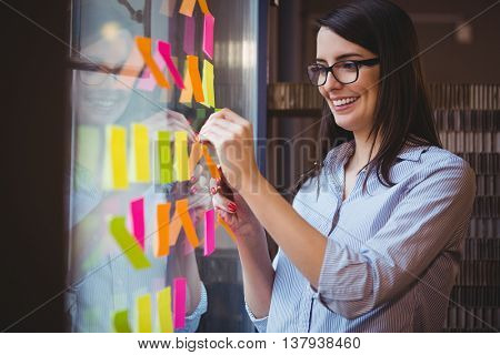 Smiling creative businesswoman sticking adhesive notes to glass in office