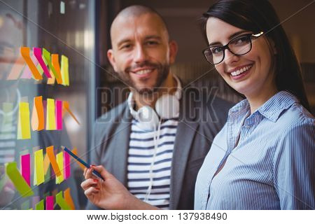 Portrait of businesswoman smiling and pointing at sticky notes while standing by male colleague in office