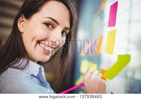 Portrait of happy creative businesswoman writing on sticky notes stuck to glass in office