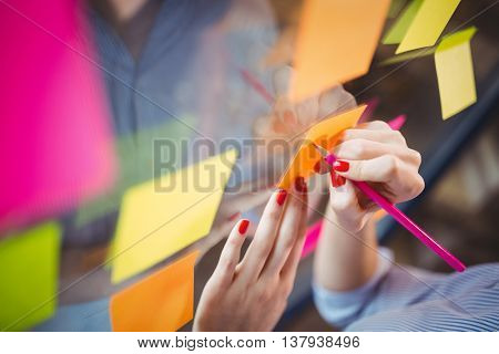 Cropped image of businesswoman writing on sticky notes stuck to glass in creative office