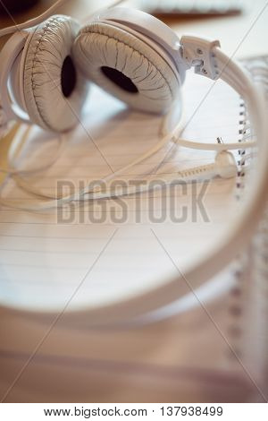 High angle view of headphones on spiral notebook