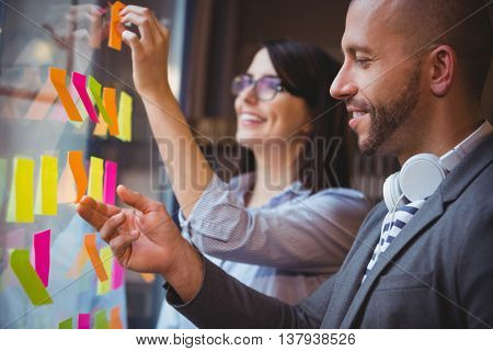 Creative coworkers sticking adhesive notes to glass in office