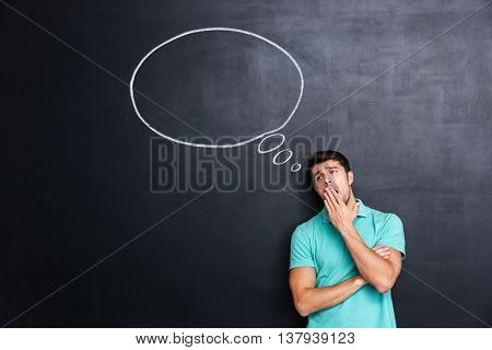 Bored tired young man standing and yawning over chalkboard background