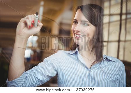 Businesswoman smiling while writing on glass with marker pen in creative office
