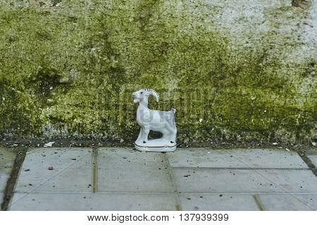 white porcelian goat near white fundation close up