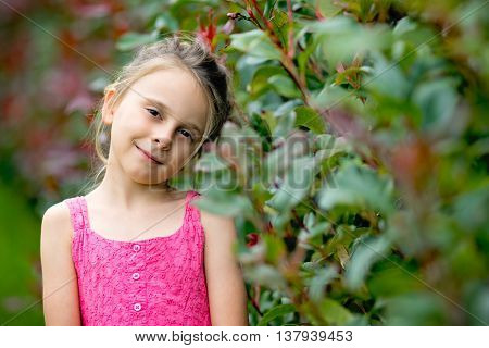 Pretty little girl smiling by green plants
