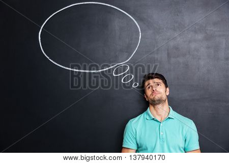 Unhappy despaired young man over blackboard background with blank speech bubble