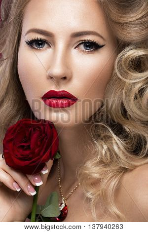 Beautiful blonde in a Hollywood manner with curls, red lips. Beauty face. Picture taken in the studio