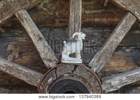 white porcelian goat on old lumber wheel