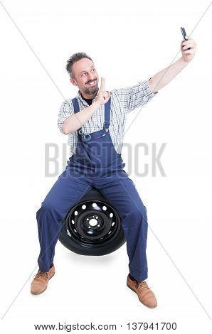 Joyful Mechanic Sitting On Tire And Taking Selfie