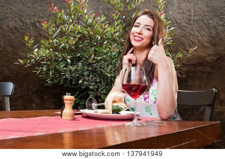 Lady Having Lunch On Terrace Showing Like Gesture
