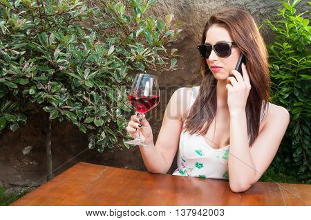 Woman Talking At Phone Raising Glass Of Wine