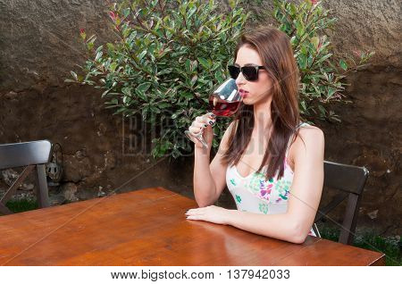 Female Sitting On Terrace Drinking Glass Of Wine