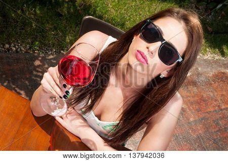 Up View Of Woman Raising Wine Wearing Sun Glasses
