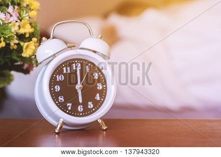 alarm clock on the bed in bedroom.