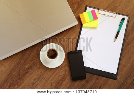 Office workplace with laptop, smart phone and coffee cup on wood table
