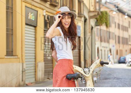 Happy young woman cyclist, biking on the old street of the city.