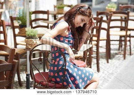 Stylish  woman, wearingsummer dresst,  posing at city cafe terrace, traveling clone, sunny day.