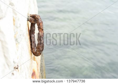 Old rustic ring for mooring boats on granite