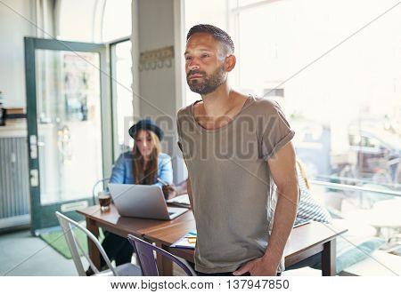 Serious Man Standing In Cafe With Open Door