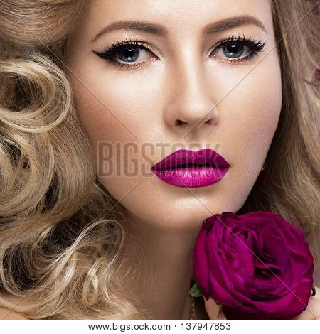 Beautiful blonde in a Hollywood manner with curls, pink lips. Beauty face. Picture taken in the studio