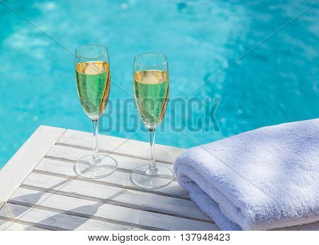 Two glasses of champagne on a white wooden table next to the swimming pool in summer.