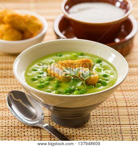 A bowl of green pea soup served with battered fish.