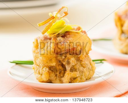 Battered stuffed artichoke heart on a plate with fresh chives and fried onion