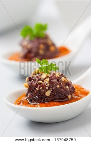 Blood and rice sausage served on a white plate with tomato sauce as appetizer.