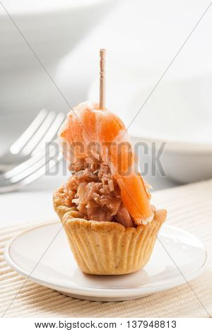 A tartlet appetizer filled with tuna fish and garnished with a shrimp.