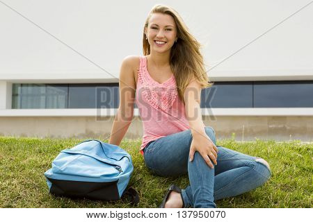 Beautiful and happy teenager sitting in the grass