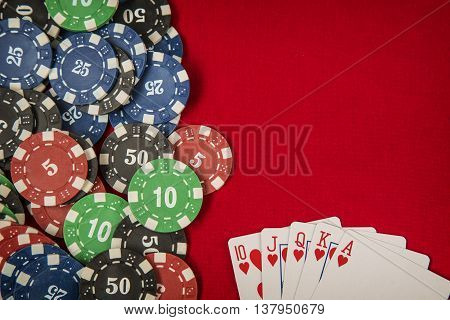Gambling chips frame and flush royal on red card table background